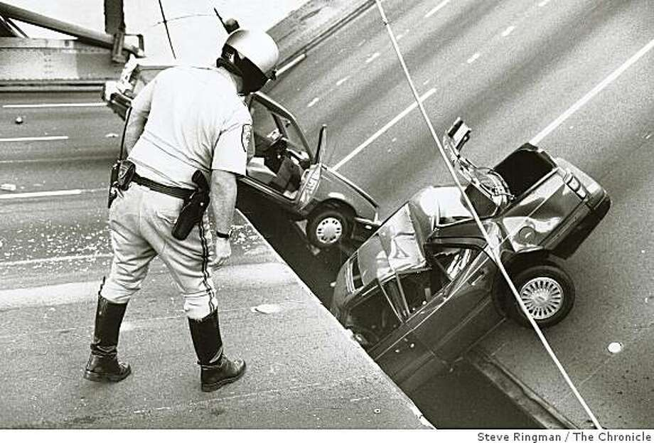 A CHP officer checks the damage to cars that fell when the upper deck of the Bay Bridge collapsed onto the lower deck on October 17, 1989. Loma Prieta Earthquake. Photo: Steve Ringman, The Chronicle