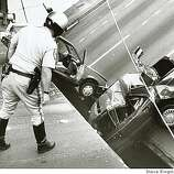 A CHP officer checks the damage to cars that fell when the upper deck of the Bay Bridge collapsed onto the lower deck on October 17, 1989. Loma Prieta Earthquake.