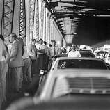 October 17, 1989 - People mill around their cars after being stopped by CHP on the Bay Bridge after the Loma Prieta earthquake.