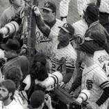 Oakland Athletics and San Francisco Giants players push up against the backstop at they try to speak to friends and family members in the stands in the moments following the Loma Prieta Earthquake during game 3 of the World Series on October 17, 1989, at Candlestick Park in San Francisco, Calif.