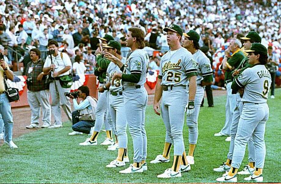 FILE--Members of the Oakland Athletics, including Mark McGwire (25), Storm Davis (left of McGwire), Jose Canseco (behind and just right of McGwire) and Mike Gallego (far right), stand and stare as Candlestick Park-goers leave the stadium in the wake of the major earthquake that struck Northern California just before game 3 of the World Series against the San Francisco Giants in this Oct. 17, 1989 file photo. With both teams again in this year's postseason, water cooler philosophers are speculating whether history will repeat. (AP Photo/FILE) Photo: File, AP