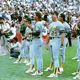 Members of the Oakland Athletics, including Mark McGwire (25), Storm Davis (left of McGwire), Jose Canseco (behind and just right of McGwire) and Mike Gallego (far right), stand and stare as Candlestick Park-goers leave the stadium in the wake of the major earthquake that struck Northern California just before game 3 of the World Series against the San Francisco Giants in this Oct. 17, 1989 file photo.