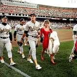 In this photo taken On October 17, 1989, Oakland A's Jose Canseco walks off the field with his wife Ester  and other A's players before the start of the World Series at Candlestick Park in San Francisco. Oct. 17, 2009 marks the 20th anniversary of the Loma Prieta earthquake. (AP Photo/Contra Costa Times, Dan Rosenstrauch)