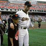 Will Clark #22 of the San Francisco Giants and his son gather on the field after a 7.1 magnitude earthquake struck the Bay Area, postponing Game three of the 1989 World Series against the Oakland Athletics at Candlestick Park on October 17, 1989 in San Francisco, California.  (Photo by Otto Greule Jr/Getty Images)