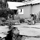 John Tranbarger cooks dinner on his barbeque in front of his powerless home in the Santa Cruz mountains. A huge crack caused by the 7.0 Loma Prieta, October 17, 1989 earthquake runs through his yard.