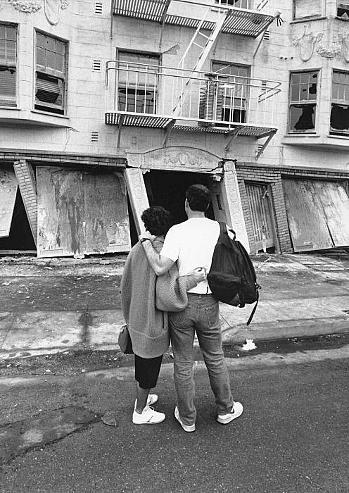 Two residents of the Marina district stand in front of their collapsed apartment building. Loma Prieta earthquake.
