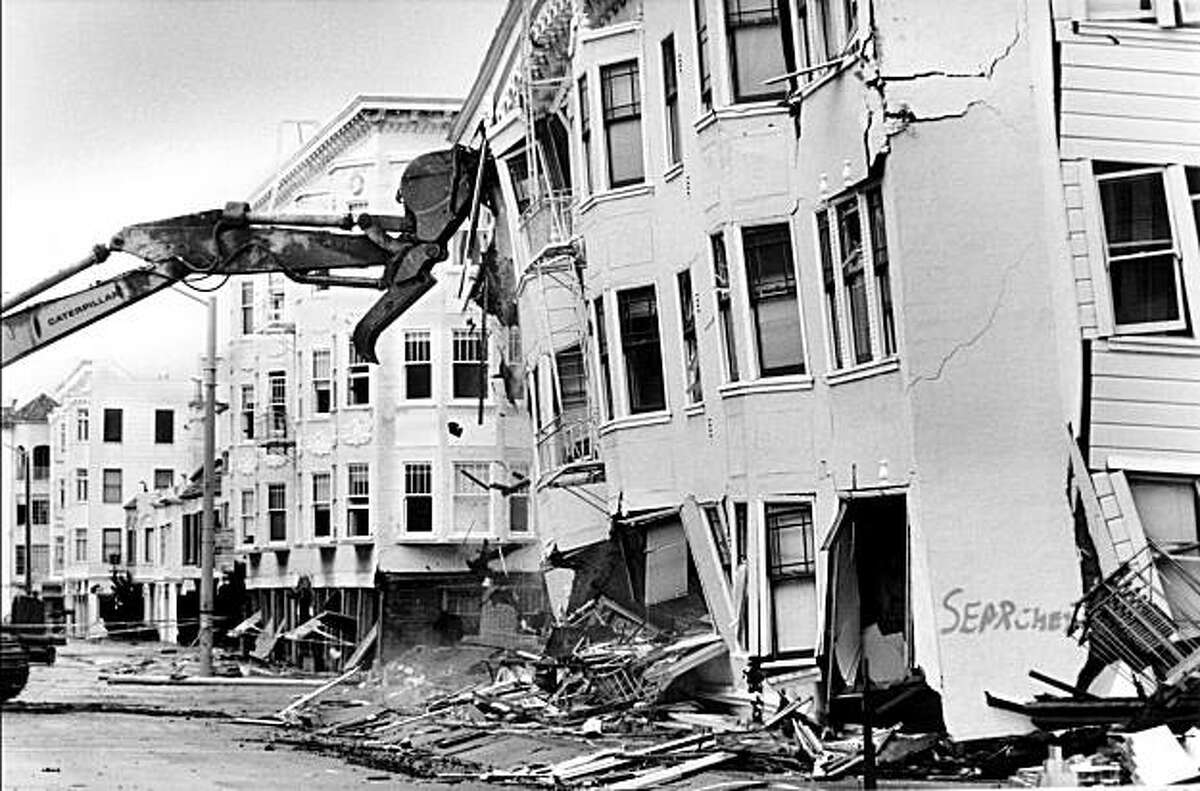 A caterpillar machine demolishes an earthquake-damaged building on Jefferson at Divisadero in the Marina district on October 21, 1989 in San Francisco, Calif. Marina District residential buildings with ground floor garages accounted for much of San Francisco's building damage during the 1989 Loma Prieta earthquake.