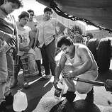 Residents line up for drinking water at the town place in Watsonville after being driven from their damaged homes after the Loma Prieta earthquake, October 17, 1989. Many have been living in tent cities in parks and school yards.