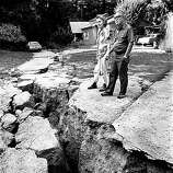 John and Freda Tranbarger stand by a huge crack that opened up in their front yard after the Loma Prieta earthquake struck. They live near the epicenter in the Santa Cruz mountains. Loma Prieta Earthquake.