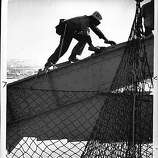 Paul Neal is stringing a safety net, which will catch anyone or anything from falling 100 feet into the water below. Bay Bridge, San Francisco, Loma Prieta earthquake.