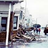 The impact of the 1989 Loma Prieta earthquake destroyed many homes, causing crews to prop up the buildings' remains with excess boards to stop them from tumbling completely.