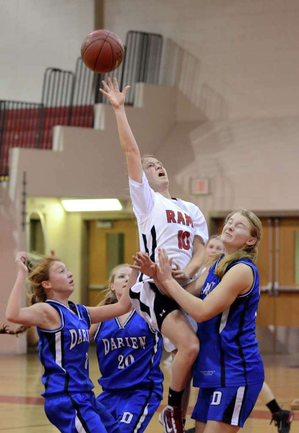 New Canaan's Sarah Mannelly (10) gets a shot off as she is fouled by Darien's Lane Davis (34) during the girls basketball game at New Canaan High School on Tuesday, Jan. 10, 2012.