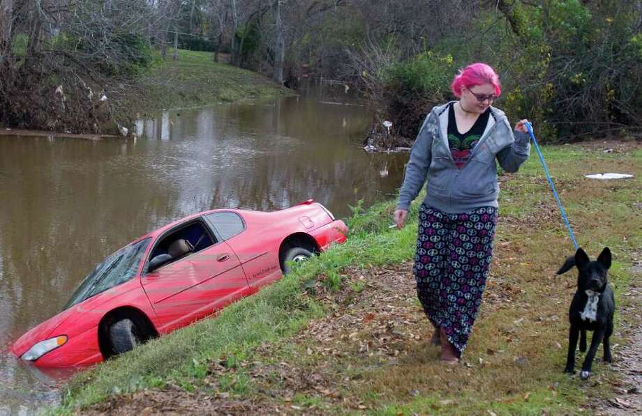 King Blvd. Animal Hospital employee Lindsay Hughes walks Duke as a car sits in Kuhlman Gully near the 5700 block of Martin Luther King Blvd. Hughes said that the last times the dogs were walked, they were standing in high water due to the flood yesterday. Photo: Cody Duty, Houston Chronicle / © 2011 Houston Chronicle
