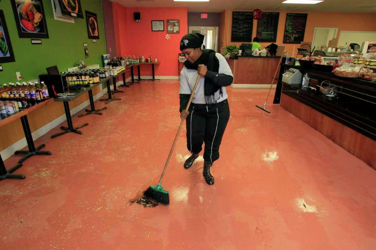 Arga Bourgeois cleans out the kitchen of Sunshine's Health Food Store after storms caused flash flooding in parts of south and southwest Houston.