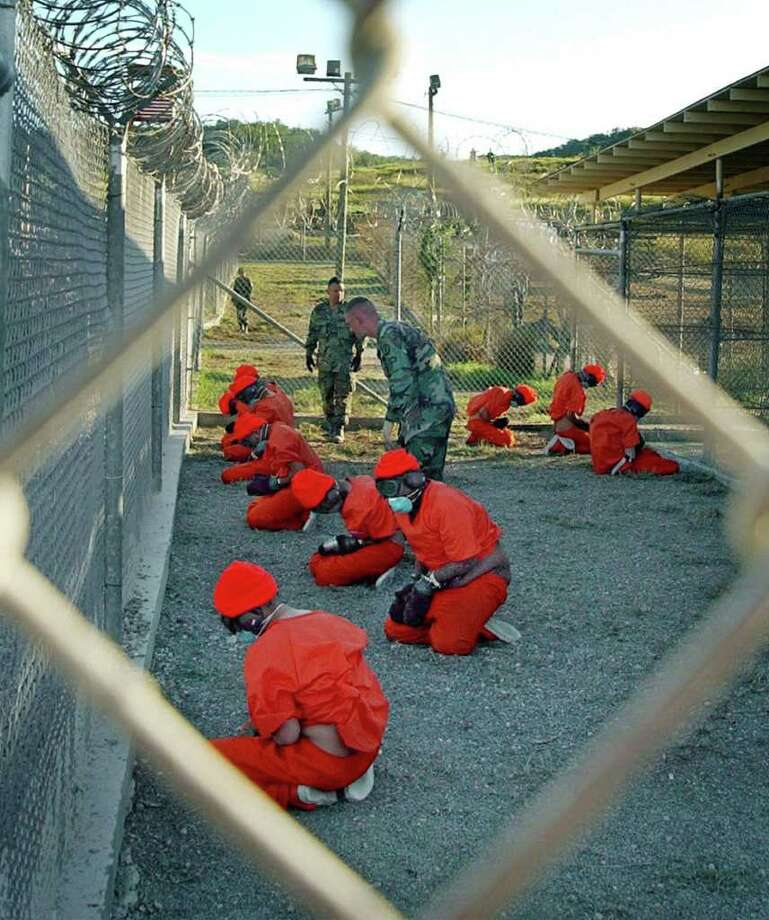 FILE - In this Jan. 11, 2002 file photo, released by the U.S. Department of Defense, detainees wearing orange jump suits sit in a holding area as military police patrol during in-processing at the temporary detention facility Camp X-Ray on Guantanamo Bay U.S. Naval Base in Cuba. Open for 10 years on Wednesday Jan. 11, 2012, the Guantanamo Bay prison seems more established than ever. The deadline set by President Barack Obama to close it came and went two years ago. No detainee has left in a year because of restrictions on transfers, and indefinite military detention is now enshrined in U.S. law. Prisoners at the U.S. base in Cuba plan to mark the day with sit-ins, banners and a refusal of meals, said Ramzi Kassem, a lawyer who represents seven inmates. (AP Photo/U.S. Navy, Shane T.McCoy, File) Photo: Shane T. McCoy