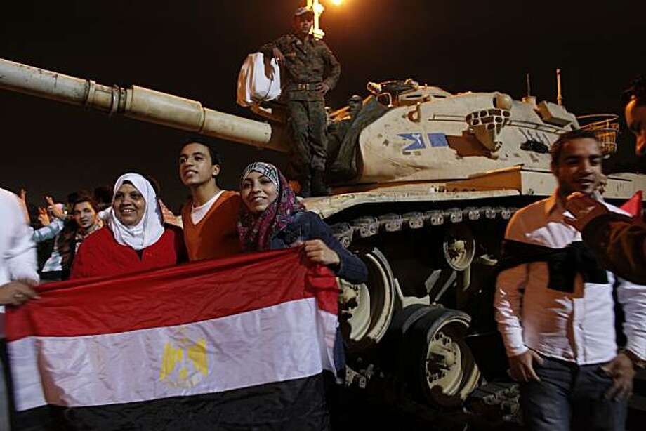 Families and protesters have their photos taken next to the Egyptian tanks as protesters erupt in joy in Cairo, Egypt's Tahrir Square following President Hosni Mubarak's announcement that he was handing power to the military on Friday, February 11, 2011. (Michael Robinson Chavez/Los Angeles Times/MCT) Photo: Michael Robinson Chavez, MCT