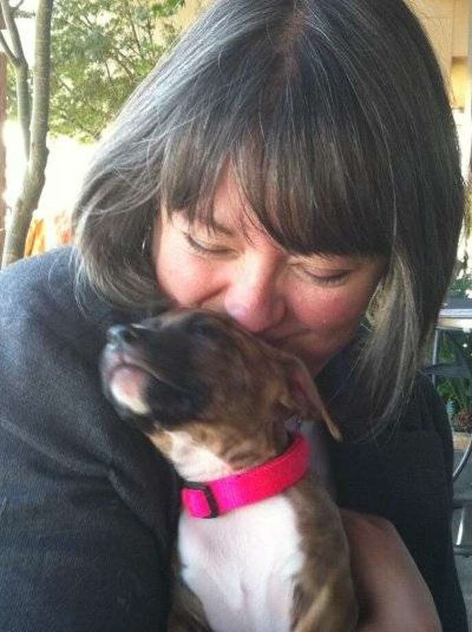 """Christie Keith with Lita, a four-month-old puppy being fostered by Sacramento's Jennifer Fearing. Despite the fact that cute puppies cause her to coo and make baby faces, Christie doesn't like to be called a """"pet parent."""" Photo: Jennifer Fearing"""