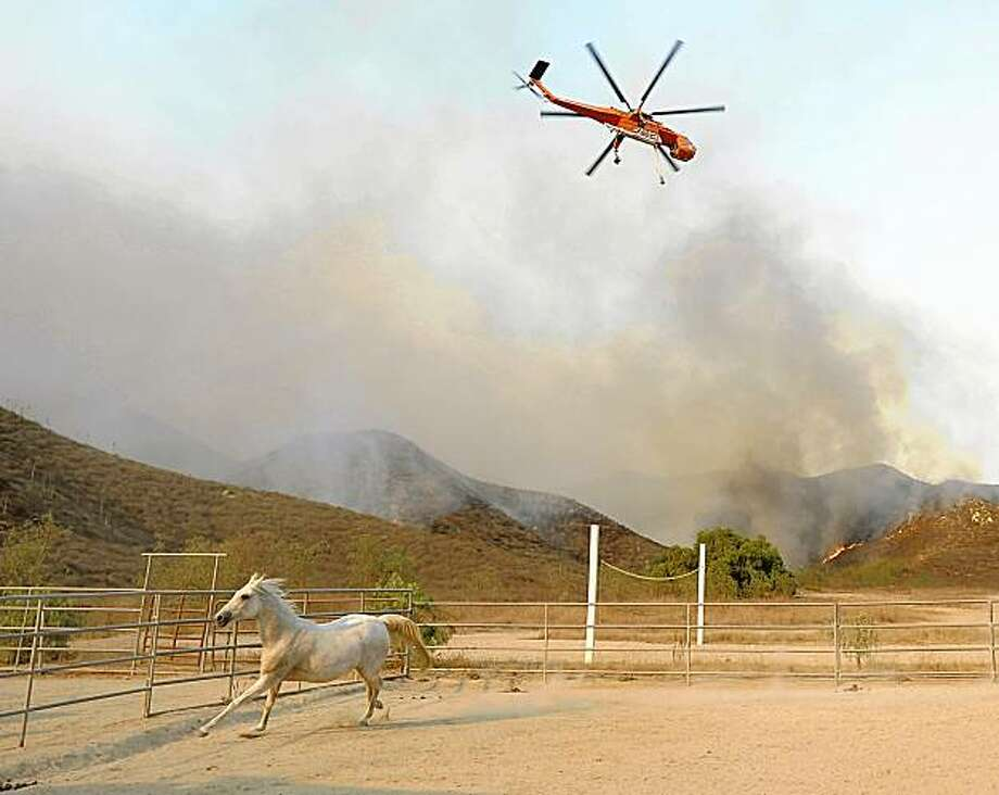 A horse runs around its corral as a helicopter makes a water drop on a fast-moving wildfire burning in the hills of Moorpark, Calif. on Tuesday, Sept. 22, 2009. New wildfires threatened homes in Southern California on Tuesday as hot and dry Santa Ana winds turned the region into a tinder box. Photo: Dan Steinberg, AP
