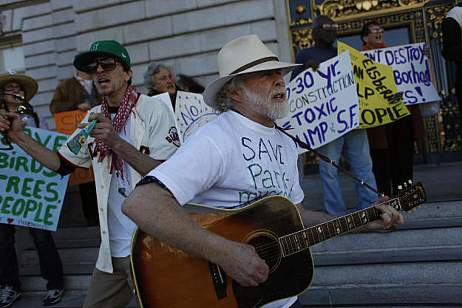 Michael Russom (right), 15 year Parkmerced resident, plays a guitar while Ben Viguerie (left), of San Francisco, plays a tambourine, while they sing songs along with others on the steps of City Hall protesting the proposed development at Parkmerced, on Thursday, February 10, 2011 in San Francisco, Calif. Photo: Lea Suzuki, The Chronicle