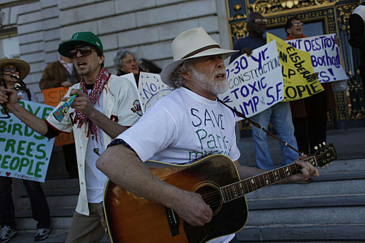 Michael Russom (right), 15 year Parkmerced resident, plays a guitar while Ben Viguerie (left), of San Francisco, plays a tambourine, while they sing songs along with others on the steps of City Hall protesting the proposed development at Parkmerced, on Thursday, February 10, 2011 in San Francisco, Calif.