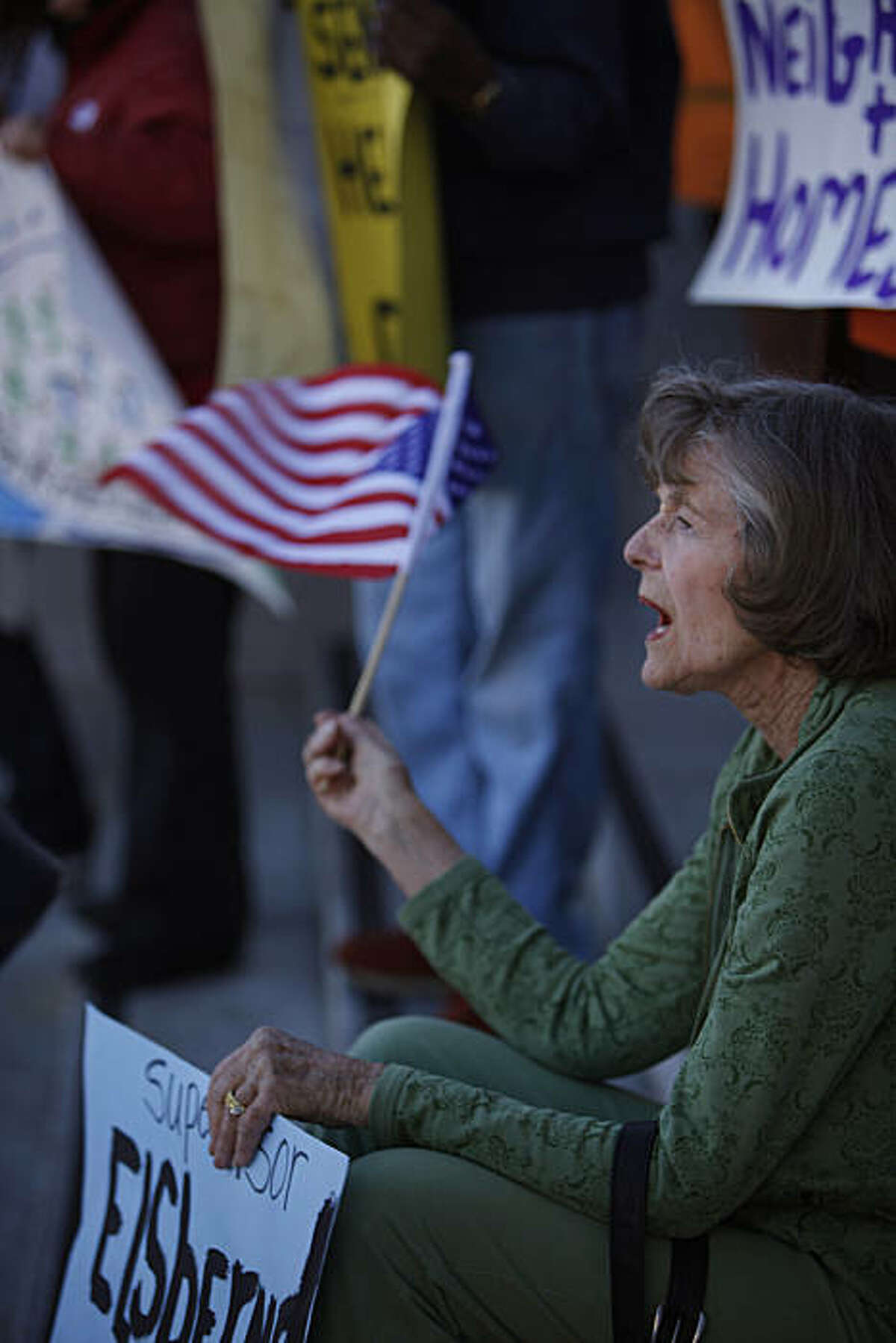 Genevieve Callejo, who has been a resident for 41 years of Parkmerced, waves an American flag as she sits on the steps of City Hall to protest the development project proposed for Parkmerced along with others on Thursday, February 10, 2011 in San Francisco, Calif.