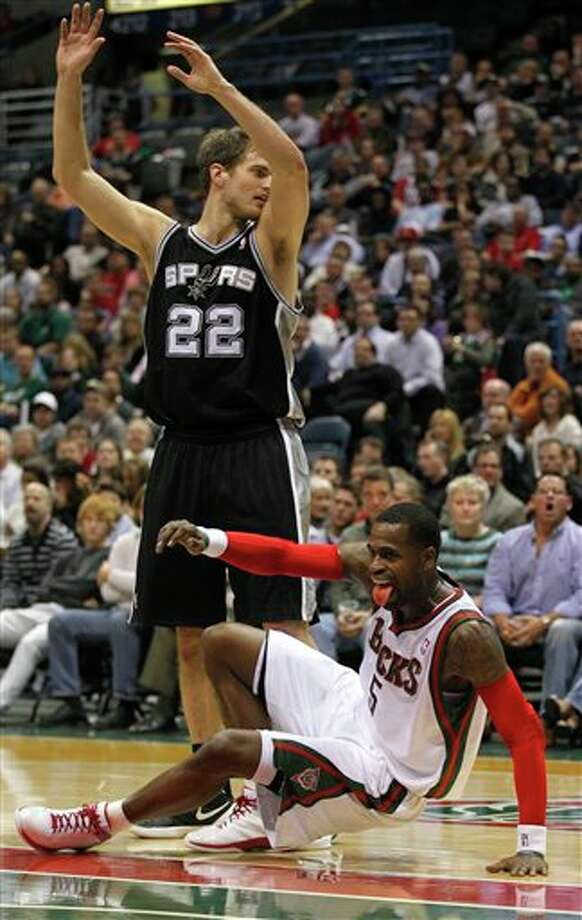 Milwaukee Bucks' Stephen Jackson, bottom, reacts after drawing an offensive foul on San Antonio Spurs' Tiago Splitter (22) during the first half of an NBA basketball game, Tuesday, Jan. 10, 2012, in Milwaukee. (AP Photo/Jeffrey Phelps) Photo: Associated Press