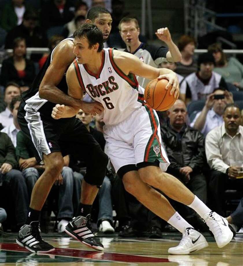 Milwaukee Bucks' Andrew Bogut (6) drives against San Antonio Spurs' Tim Duncan, left, during the first half of an NBA basketball game, Tuesday, Jan. 10, 2012, in Milwaukee. (AP Photo/Jeffrey Phelps) Photo: Associated Press