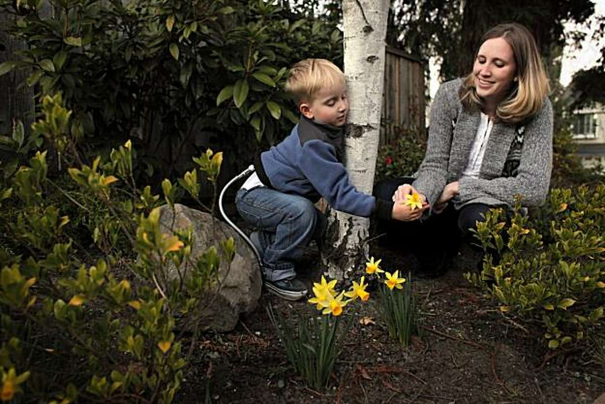 Thomas Giovanola picks a flower for his mother Heather in their garden at home, Tuesday Feb. 8, 2011, in San Ramon, Calif. The two are part of a UCSF doctors trial and were one of the first fetal surgery. The trial was looking at treatment of spina bifida, a disabling defect that occurs when part of the spinal cord forms outside of the body. When the defect is repaired while the fetus is still in the womb, instead of after birth as it's normally done, children are healthier overall and more likely to be able to walk, the study found.