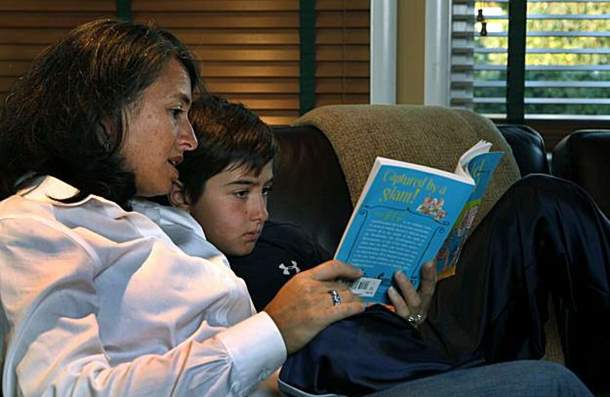 Melanie Wellbeloved reads with her son Mason age nine in their Marin County home. Mason was diagnosed with a brain tumor last year. He's recovering and back in school now, but when children get cancer, their parents sometimes develop posttraumatic stress syndrome because of the assault on their children and the never-ending fear that the cancer will recur. Saturday Jan 15, 2011.