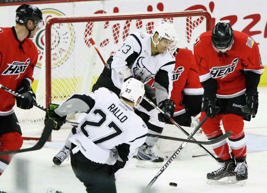 San Antonio Rampage's Wacey Rabbit (23) and Greg Rallo (27) fight for the puck with Abbotsford Heat's John Negrin, right, during the third period of an AHL hockey game, Tuesday, Jan. 10, 2012, in San Antonio. Abbotsford won 5-0. Photo: Darren Abate, Darren Abate/pressphotointl.com / Darren Abate/pressphotointl.com