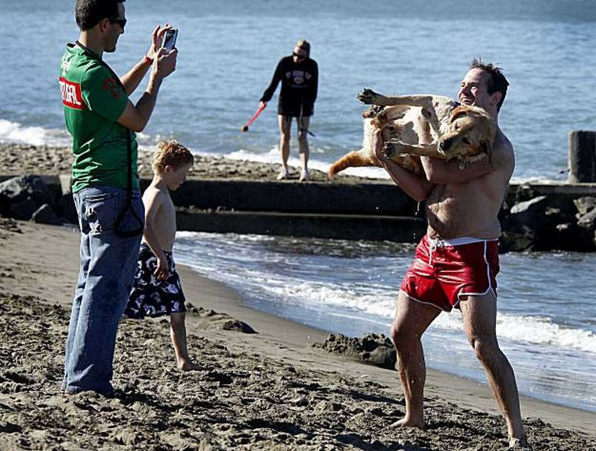 Owen Thomas (right) gets his picture taken with Indo the retriever at East Beach in San Francisco. Thomas said he has no interest in the Super Bowl. The weather was so excellent Sunday that some locals decided to skip the game and enjoy some surprising mild winter temperatures.