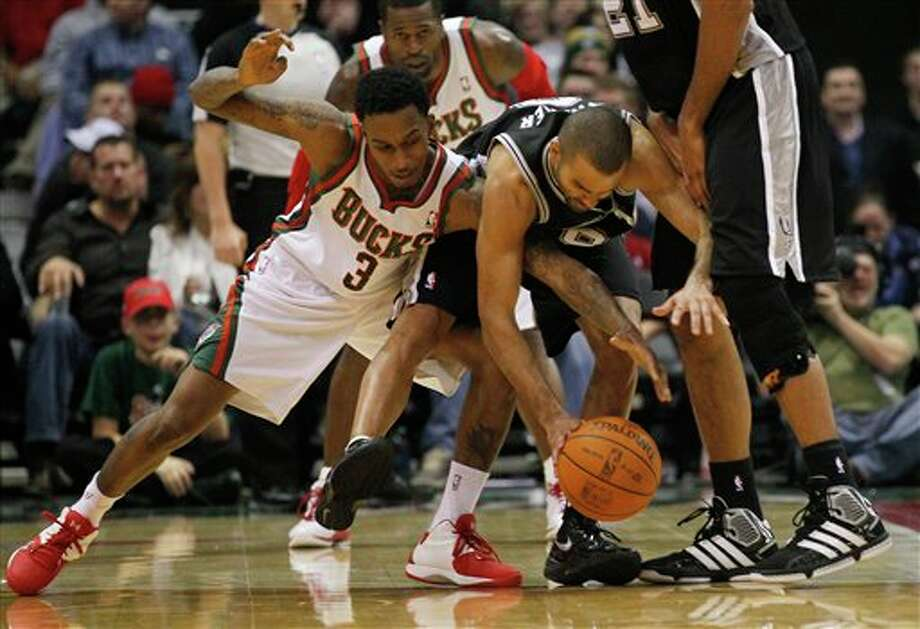 Milwaukee Bucks' Brandon Jennings (3) battles San Antonio Spurs' Tony Parker, right, of France, for a loose ball during the second half of an NBA basketball game, Tuesday, Jan. 10, 2012, in Milwaukee. The Bucks won 106-103.  (AP Photo/Jeffrey Phelps) Photo: Associated Press