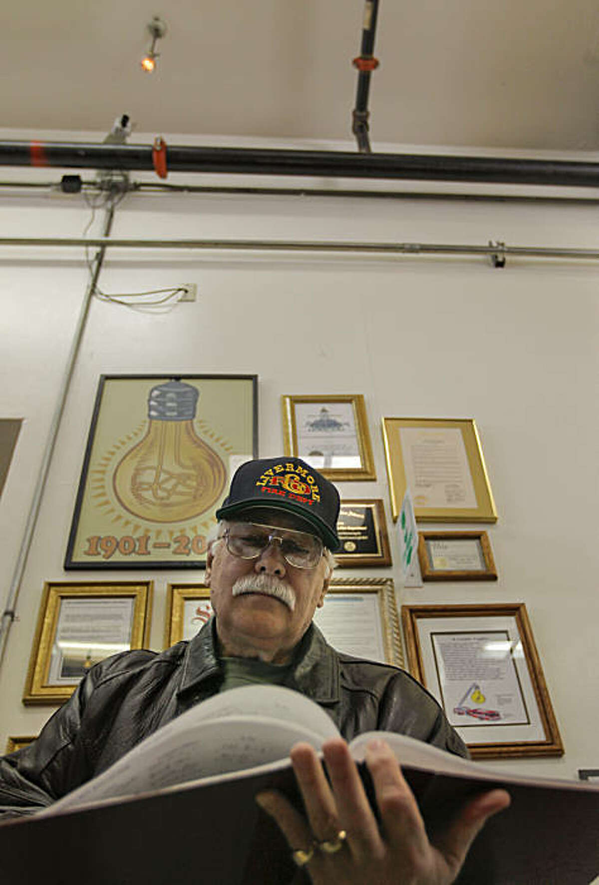 Retired Livermore Division Fire Chief, Lynn R. Owens, holds the guestbook showing visitors who have stopped by to see the longest burning light bulb, as declared by the Guinness Book of World Records and Ripley's Believe-It-or-Not, which hangs above him from the ceiling of Livermore fire Station #6 on Thursday Feb. 3, 2011, in Livermore, Ca. Owens is the chairperson of the Livermore Light Bulb Centennial Committee. A small area inside the fire station garage has been dedicated with displays in recognition of the centennial bulb. The light bulb was first switched on at fire department hose cart house on L Street in Livermore in 1901.