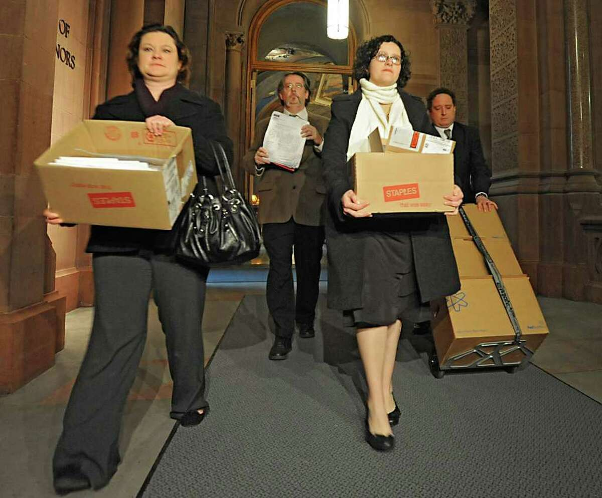 """Anti-fracking """"water rangers"""" deliver boxes of comments to Governor Cuomo's office at the Capitol Tuesday, Jan. 10, 2012 in Albany, N.Y. From left, Sarah Eckel and Bill Cooke, both from Citizens Campaign for the Environment, Katherine Nadeau, Environment Advocates of N.Y. and Roger Downs of the Sierra Club. (Lori Van Buren / Times Union)"""