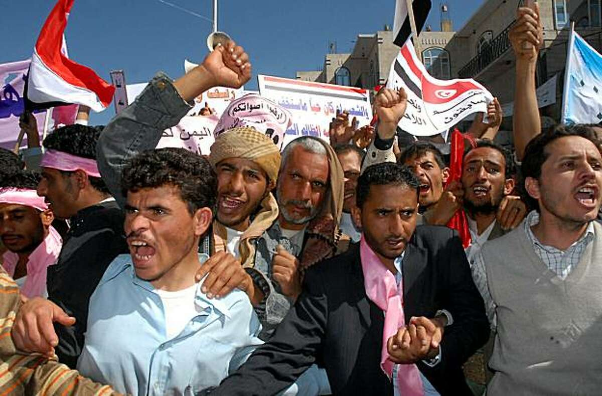 Yemeni anti-government protesters shout slogans during a
