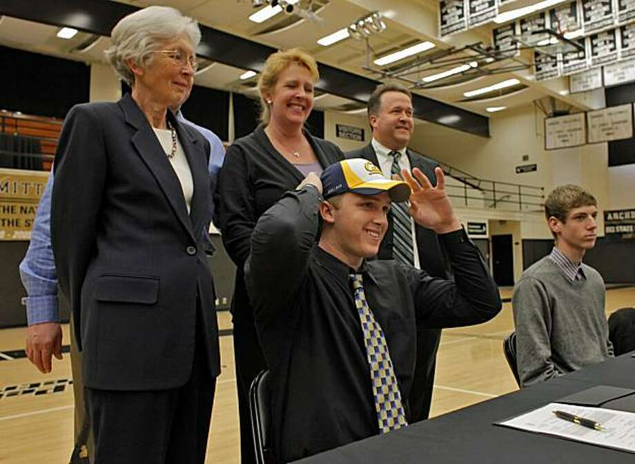 Archbishop Mitty  High School football players Kyle Boehm puts his cap on after signing a four year scholarship from UC Berkeley, with his  grandmother, Barbara Titel,  father Dale Boehm,  mother Carrie Simons and head coach Matt Haniger, Tuesday Feb. 2, 2011, in San Jose, Calif. Swimmer Jeremie DeZwirek, right, also signed a scholarship at Columbia University in New York. Photo: Lacy Atkins, The Chronicle