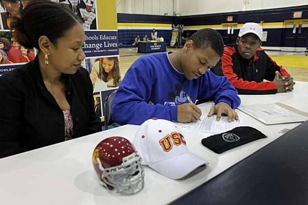 King's Academy High School football player Amir Carlisle, center, signs a four year scholarship to USC with his mother Shereese and father Duane by his side, Tuesday Feb. 2, 2011, in Sunnyvale, Calif. Photo: Lacy Atkins, The Chronicle