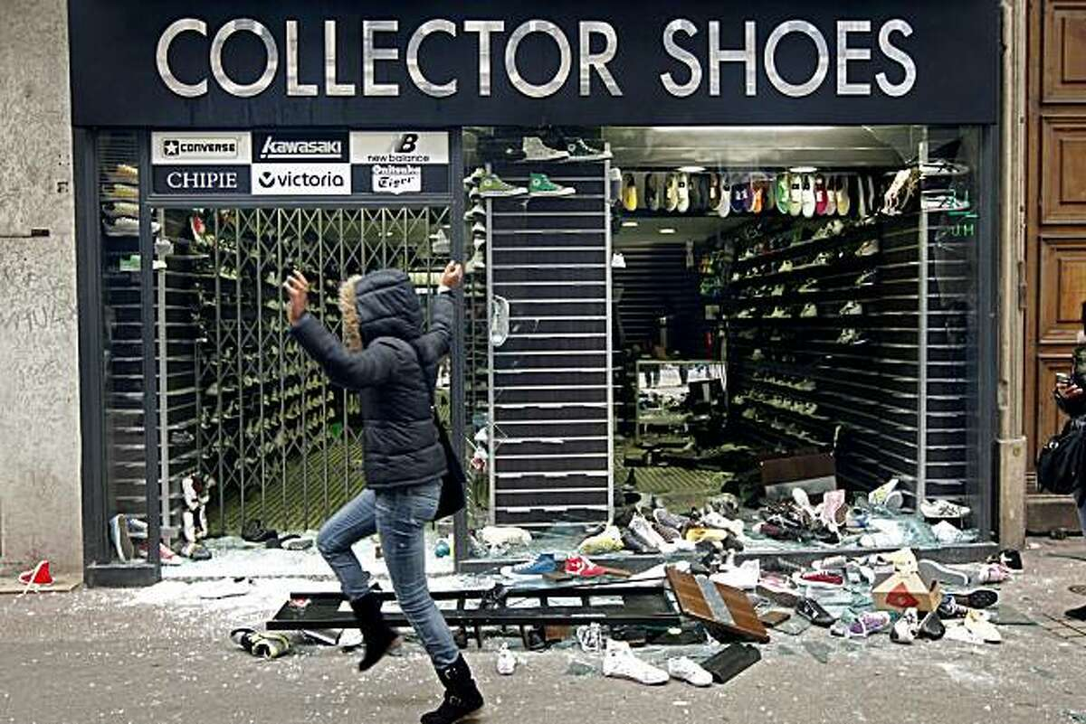 A woman runs past a devastated shoe shop during clashes in Lyon, central France, Tuesday, Oct. 19, 2010. Some airliners steered clear of France and police clashed with stone-throwing youths Tuesday as a new round of nationwide strikes and protests over abill raising the retirement age to 62 kicked off.