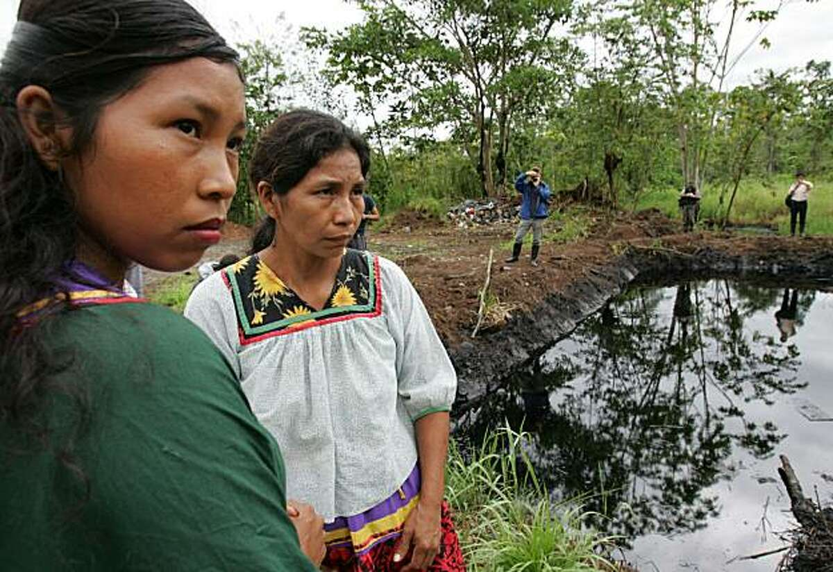 ** FILE ** Cofan indigenous women stand near an open oil pit in the Sucumbios province in Ecuador's Amazon in this Wednesday, Oct. 19, 2005 file photo. A court-appointed expert recommended on April 2, 2008 that Chevron Corp. pay up to US$16 billion (10.2 billion) for allegedly polluting Ecuador's Amazon in a class-action suit by 30,000 jungle settlers and Indians. (AP Photo/Dolores Ochoa)