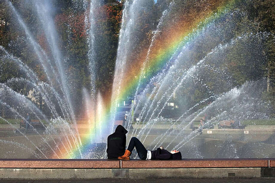The magnificent fall weather and sunny skies bring people to the Seattle Center Sunday Oct. 17, 2010 and creates a rainbow in the spray from the fountain.  Henry Halvorson, left, and Charlie Kennedy enjoy the brilliant afternoon. Photo: Dean Rutz, Seattle Times