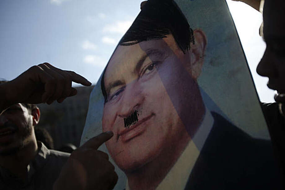 Chaos has enveloped Egypt in the wake of massive protests and widespread violence against the regime of President Hozni Mubarak. Protestors are getting increasingly creative with their signs, like this one likening Mubarak to Nazi dictator Adolf Hitler.  (Michael Robinson Chavez/Los Angeles Times/MCT) Photo: Michael Robinson Chavez, MCT