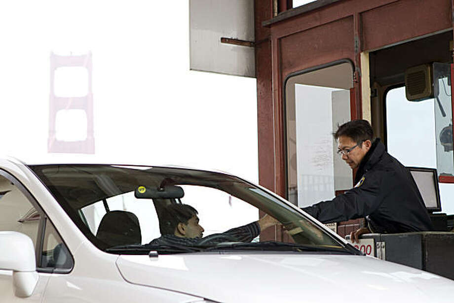 Ben Ramirez collects a toll from a motorist while working at the Golden Gate Bridge in San Francisco, Calif., on Friday, January 28, 2011.  Starting in 2012, the bridge will no longer be using toll takers and will move to an all-electronic system. Photo: Laura Morton, Special To The Chronicle