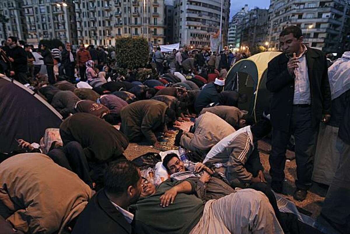 Anti-government protesters chat as others pray behind them in Tahrir Square in Cairo, Egypt, Monday, Jan. 31, 2011. A coalition of opposition groups called for a million people to take to Cairo's streets Tuesday to demand the removal of President Hosni Mubarak.