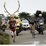 Dore Holt , a cycling fan from Seattle, WA., wears Rocky Mountain Elk horns as he runs up the steep Coleman Valley Road just north of Bodega Bay with race leader Jackson Stewart of the BMC Racing team. Stewart had an 11 minute lead from the peloton at this point in the Amgen Tour of California.