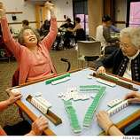 Jane Louie, 80, puts her hands up in fun and frustration after her long-time friend Michi Handa, 77, calls mahjong during the weekly meeting of the Fremont Senior Center Mahjong Group.