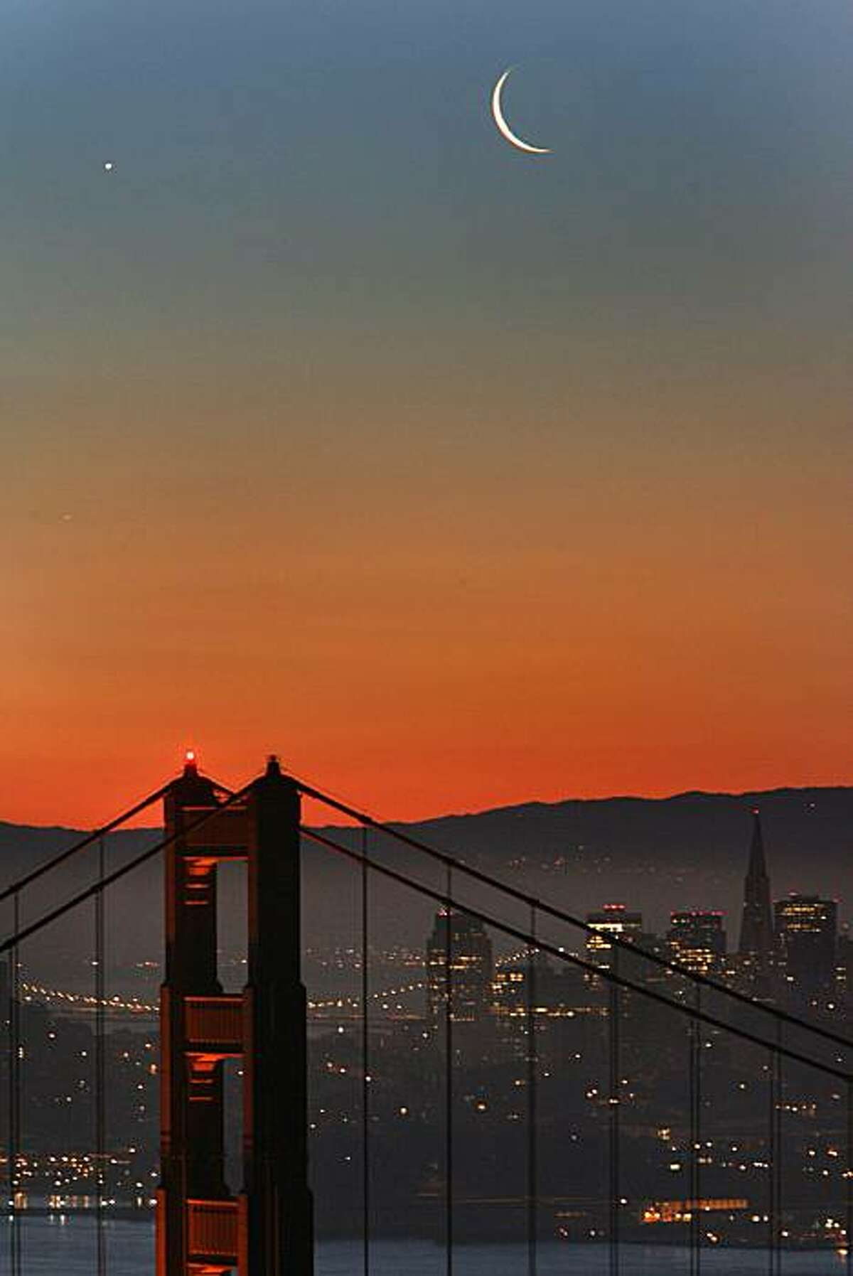 Seen from the Marin headlands rising over the north tower of the Golden Gate Bridge was both the crescent moon and the planet Venus pairing up within minutes of each other during the morning twilight on March 5, 2008. 3/5/08. {Photo by Frederic Larson / San Francisco Chronicle}