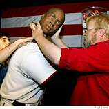 Eric Valencia, left, and museum curator Curtis Huber reattach Barry Bonds' head after relocating the figure from a coveted main lobby location at the Wax Museum in San Francisco, Calif., on Wednesday, April 16, 2008.