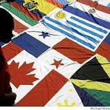 Seventeen year-old flag bearer Ravon Anderson of San Francisco looks at the multi-nation flags that were sewn together and were to be carried at the front of an immigrant rights march from Dolores Park to City Hall in San Francisco, Calif., on Thursday, May 1, 2008.