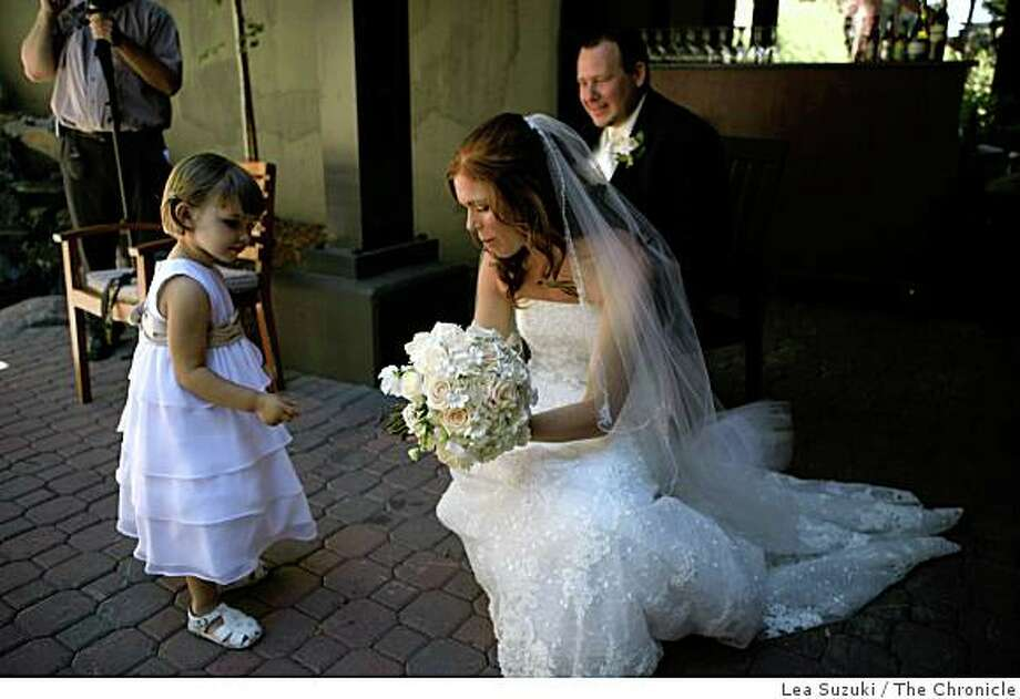 Flower girl Bella Godleski 3, inspects Carrie Shellhammer's (center) bouquet while she and Zachary Chown (back right) pose for wedding photos at The Lodge at Tahoe Donner before their wedding in Truckee, Calif. on Saturday, August 9, 2008.Ran on: 08-11-2008Flower girl Bella Godleski inspects bride Carrie Shellhammer's bouquet. Groom Zachary Chown sits in back.Ran on: 08-11-2008Flower girl Bella Godleski inspects bride Carrie Shellhammer's bouquet. Groom Zachary Chown sits behind. Photo: Lea Suzuki, The Chronicle