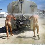 Two naked men follow a water truck through the camps at Burning Man to get a quick shower at Black Rock NV, on August 29, 2008.